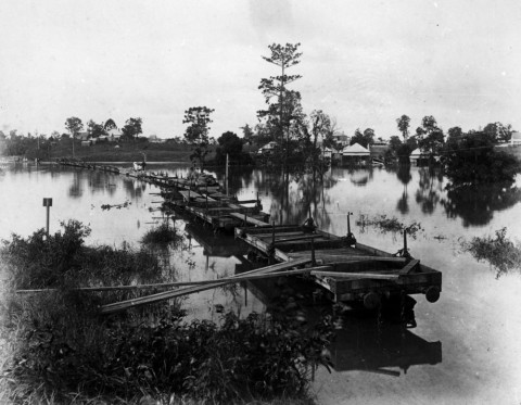 Makeshift bridge of railway wagons during the 1890 flood in Auchenflower. (State Library of Queensland, Negative no. 22684)