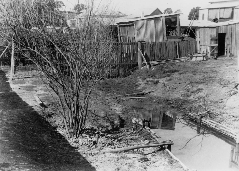 An open drain in a backyard at Ellena Street, c1905. This would have been the sorry state of many tributaries of Western Creek, including the one in Rhonda's backyard. Covering these trenches would have alleviated smells and safety concerns, but created new problems when high volumes of water gushed through the catchment. (State Library of Queensland, Image no. 47486)